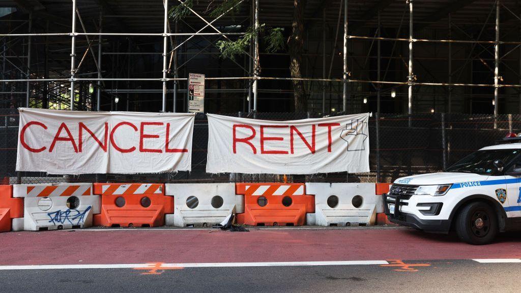 """strongUn vehículo de la policía de Nueva York se estaciona frente al letrero que dice """"eliminen la renta"""" que fue colgado por participantes del mitin """"Resist Evictions"""" para protestar contra los desalojos, el 10 de agosto de 2020, en la ciudad de Nueva York. (Michael M. Santiago/Getty Images)/strong"""
